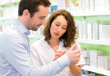 advising: VIew of an Attractive pharmacist advising a customer