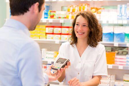 healt: View of an Attractive pharmacist taking healt insurance card