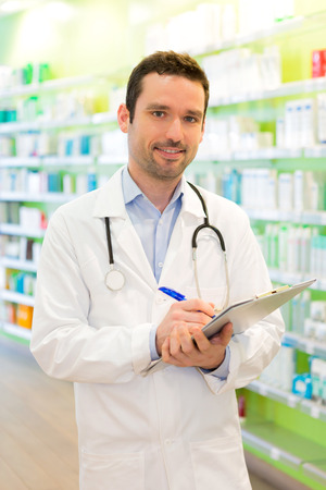 medecine: View of a Attractive pharmacist taking notes at work Stock Photo