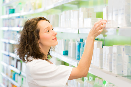 medecine: VIew of an Attractive pharmacist clean the store up