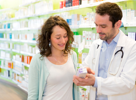 VIew of an Attractive pharmacist advising a patient