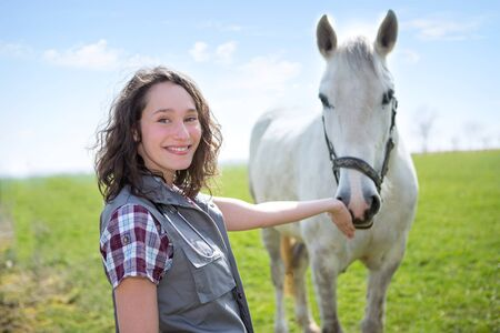 veterinaria: Vista de una joven veterinaria atractiva en campos con caballo Foto de archivo