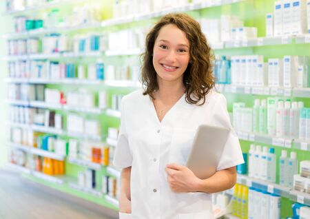 pharmacist: VIew of an Attractive pharmacist using tablet at work
