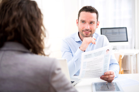 View of a Young attractive employer analysing resume of woman Stock Photo