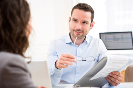 job interview: View of a Young attractive employer analysing resume of woman Stock Photo
