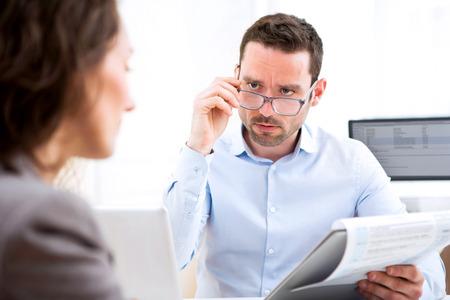 Vue d'un jeune, séduisant employeur analyse CV de la femme