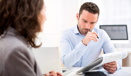 resume: View of a Young attractive employer analysing resume of woman Stock Photo