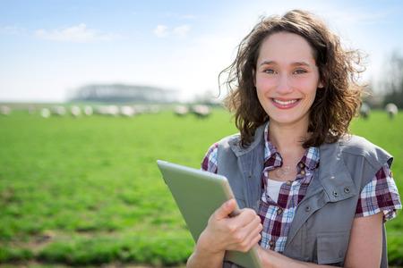 Vue d'un jeune agriculteur attrayant dans un champ en utilisant la tablette