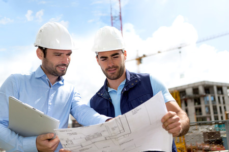 construction sites: View of an Engineer and worker checking plan on construction site
