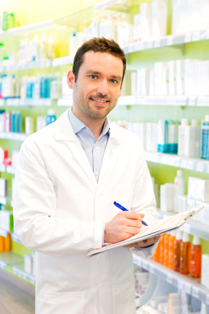 medecine: Vjew of a Attractive pharmacist taking notes at work Stock Photo