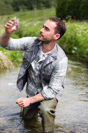 View of a Biologist take a sample in a river in order to do some test Stock Photo