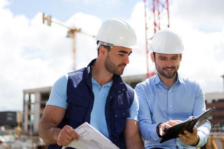 建築家と労働者が建設現場でミーティングを計画のビュー