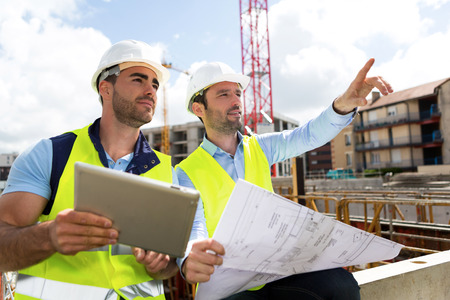 obrero trabajando: Vista de un Trabajador y arquitecto viendo algunos detalles en una construcción Foto de archivo