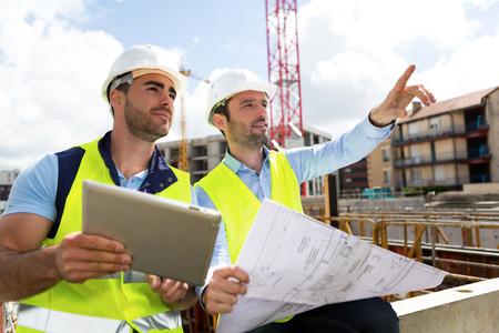 ouvrier: Vue d'un travailleur et architecte regarder quelques détails sur une construction Banque d'images