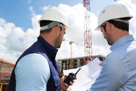 View of a Engineer and worker watching blueprint on construction site Stockfoto