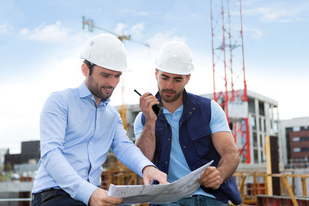 building site: View of a Engineer and worker watching blueprint on construction site Stock Photo