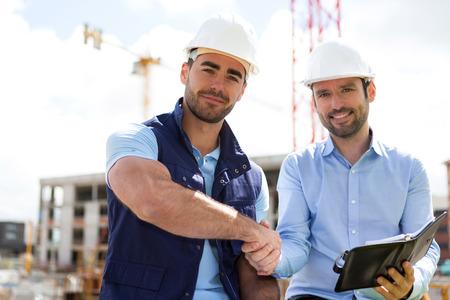 建設現場での建築家および労働者のハンド シェークのビュー