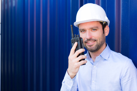 talkie: View of a Young Attractive engineer using talkie walkie on the dock