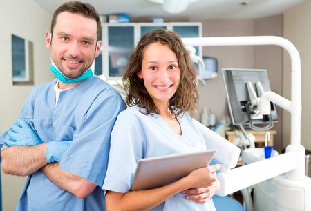dentista: Vista de un Retrato de una joven atractiva dentista y su asistente en su oficina Foto de archivo