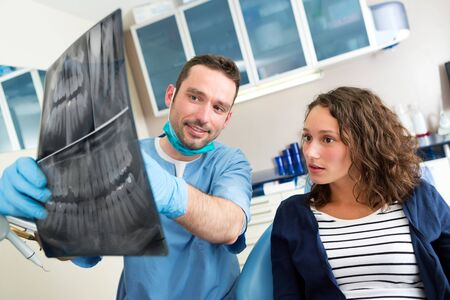 explanations: View of a Young attractive dentist showing x-ray to patient Stock Photo