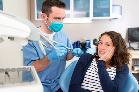 asustado: Vista de una mujer atractiva joven asustado de ser curado por un dentista