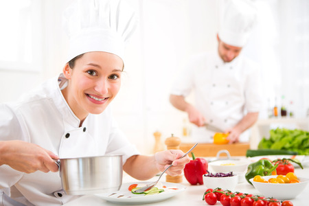 View of a Young attractive professional chef cooking in his kitchen
