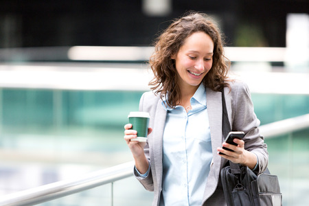 View of a Young attractive business woman using smartphone drinking coffee