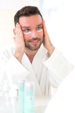thirties: View of a Young attractive man applying anti dark circles cream around eyes