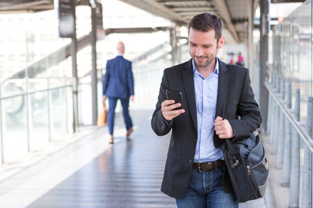 young man smiling: View of a Young attractive business man using smartphone Stock Photo