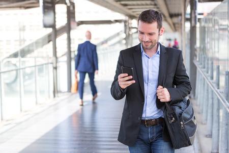 persona caminando: Vista de un joven atractivo tel�fono inteligente hombre de negocios usando Foto de archivo