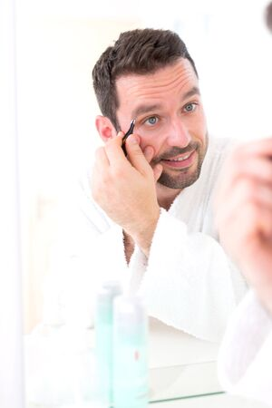 tweezing eyebrow: View of a Young attractive man tweezing his eyebrow