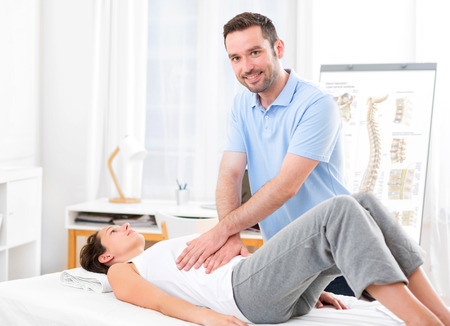 View of an Young attractive woman being manipulated by physiotherapist Stock Photo