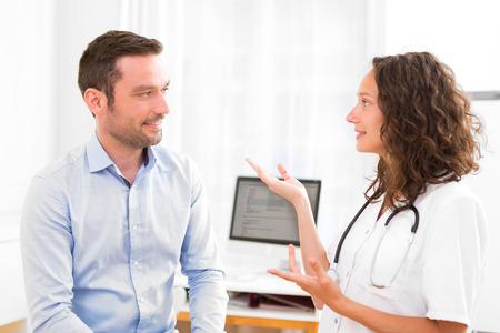 medico con paciente: Vista de un doctor atractivo joven que escucha su paciente