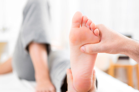 foot pain: View of a Young attractive physiotherapist doing reflexology on a patient feet