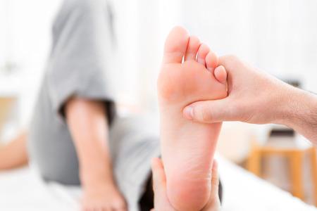 pena: Vista de una joven fisioterapeuta atractiva haciendo reflexología en un paciente pies