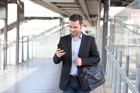 View of a Young attractive business man using smartphone Banco de Imagens