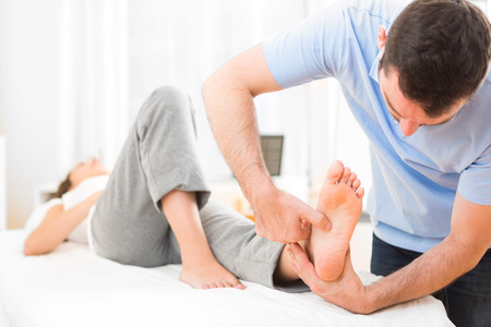 View of a Young attractive physiotherapist doing reflexology on a patient feet