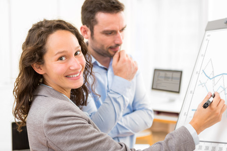 paperboard: View of  Business man and woman analysing stats on a paperboard