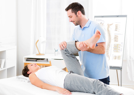medecine: View of a Young attractive woman being manipulated by physiotherapist Stock Photo