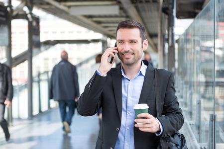 personas caminando: Vista de un hombre de negocios atractivo joven que usa el tel�fono inteligente, mientras que el consumo de caf� Foto de archivo