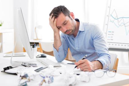 persona deprimida: Vista de un hombre joven atractivo demasiado cansado para trabajar Foto de archivo