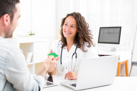 View of a Young attractive doctor taking health insurance card
