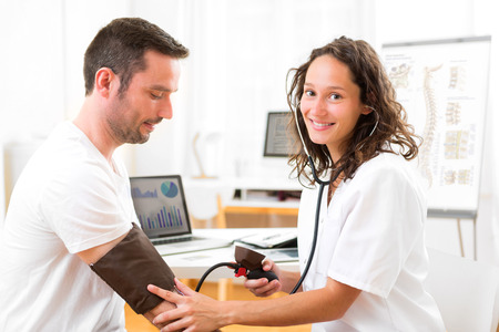 View of a Young attractive doctor checking patients blood pressure