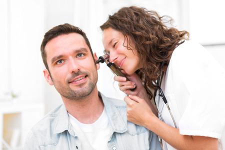 젊은 매력적인 의사의보기는 환자의 귀를 검사