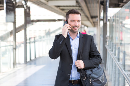 businessman walking: View of a Young attractive business man using smartphone Stock Photo