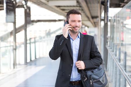 persona caminando: Vista de un joven atractivo teléfono inteligente hombre de negocios usando Foto de archivo