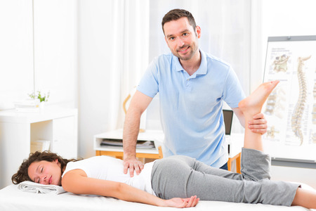 manipulated: View of a Young attractive woman being manipulated by physiotherapist Stock Photo