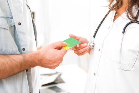 醫療保健: 查看一個年輕漂亮的醫生以醫療保險卡