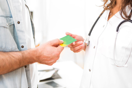 Blick auf ein Junge attraktive Arzt, die Krankenversicherungskarte Standard-Bild - 46289242