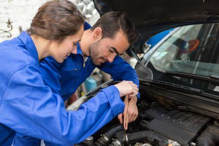 mecanico: Vista de un equipo de mecánicos que trabajan en el garaje